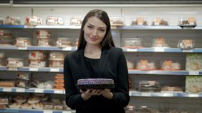 Jolie femme posant devant le contre- café et tarte de présentation au supermarché Photo stock