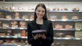 Jolie femme posant devant le contre- café et tarte de présentation au supermarché Image stock