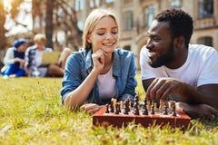 Jolie femme positive enseignant son ami jouant des échecs Images libres de droits