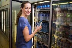 Jolie femme prenant la bouteille de l'eau dans le réfrigérateur Photographie stock libre de droits