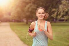 Jolie femme pulsant au parc avec des écouteurs photo stock