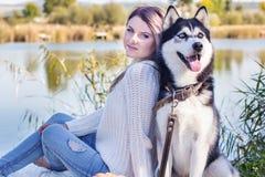 Jolie femme que son chien d'ami se repose près du lac Photos libres de droits