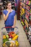 Jolie femme réfléchie poussant le chariot dans le bas-côté Photo libre de droits