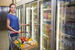 Jolie femme regardant l'appareil-photo et prenant le produit sur le réfrigérateur Photographie stock libre de droits