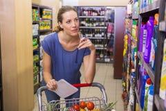 Jolie femme regardant le produit sur l'étagère et tenant la liste d'épicerie Photo stock