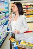Jolie femme regardant le produit sur l'étagère et tenant la liste d'épicerie Photographie stock libre de droits