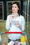 Jolie femme regardant le produit sur l'étagère et tenant la liste d'épicerie Photos stock