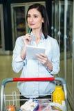 Jolie femme regardant le produit sur l'étagère et tenant la liste d'épicerie Image stock