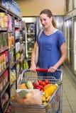 Jolie femme regardant le produit sur l'individu Photo stock