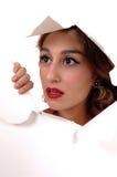 Jolie femme regardant par un trou Photos stock