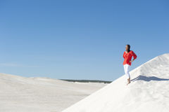 Jolie femme restant confiante sur la dune de désert Image stock