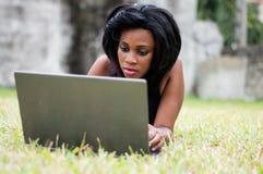 Jolie femme s'étendant sur l'herbe et travaillant sur l'ordinateur portable photo libre de droits