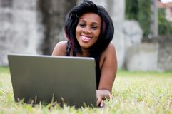 Jolie femme s'étendant sur l'herbe et travaillant sur l'ordinateur portable photos stock
