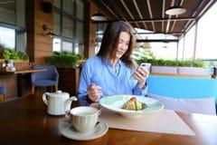 Jolie femme s'asseyant au café, causant par le smartphone et ayant Photos stock