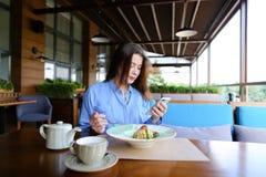 Jolie femme s'asseyant au café, causant par le smartphone et ayant Photographie stock libre de droits
