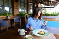 Jolie femme s'asseyant au café, causant par le smartphone et ayant Images stock