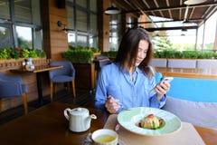 Jolie femme s'asseyant au café, causant par le smartphone et ayant Images libres de droits