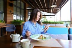 Jolie femme s'asseyant au café, causant par le smartphone et ayant Photographie stock
