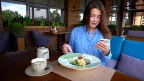 Jolie femme s'asseyant au café, causant par le smartphone et ayant Image libre de droits