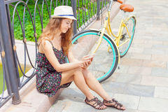 Jolie femme s'asseyant au pont près de la bicyclette de vintage, sms de dactylographie Image libre de droits