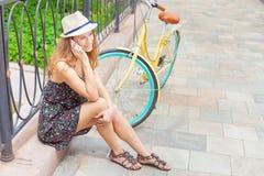 Jolie femme s'asseyant au pont près de la bicyclette de vintage, sms de dactylographie Photographie stock libre de droits