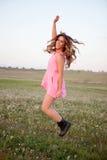 Jolie femme sautant sur un pré fleuri Images stock