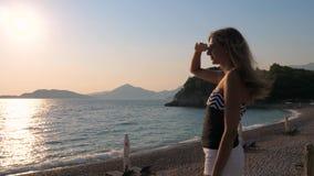 Jolie femme se tenant sur la plage appréciant observant le mouvement lent 4K de coucher du soleil clips vidéos