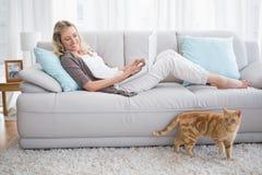 Jolie femme se trouvant sur le sofa utilisant son ordinateur portable images libres de droits