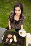 Jolie femme souriant faisant cuire la nourriture d'arrière-cour de barbecue de biftecks Photographie stock libre de droits