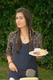 Jolie femme souriant faisant cuire le gril de nourriture d'arrière-cour de barbecue de biftecks Image stock