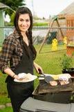 Jolie femme souriant faisant cuire le gril de nourriture d'arrière-cour de barbecue de biftecks Photo libre de droits