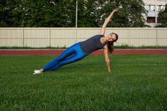 Jolie femme sportive s'étirant avant séance d'entraînement à la pelouse L'espace pour le texte photographie stock libre de droits