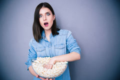 Jolie femme stupéfaite mangeant du maïs éclaté Photo libre de droits