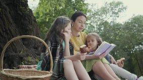 Jolie femme sup?rieure de portrait s'asseyant sur la couverture sous l'arbre en parc lisant le livre Deux adorables clips vidéos