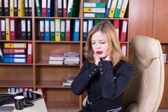 Jolie femme surchargée dans le bureau avec douleur cervicale Photographie stock