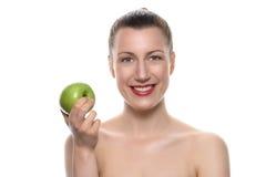 Jolie femme tenant Apple vert contre le blanc Image libre de droits