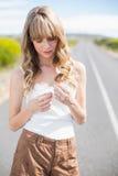 Jolie femme tenant la fleur tout en marchant sur la route Photos libres de droits
