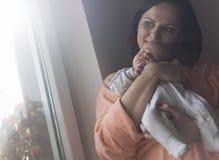 Jolie femme tenant un bébé nouveau-né dans des ses bras image libre de droits