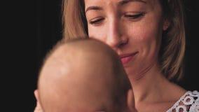 Jolie femme tenant un bébé nouveau-né dans des ses bras banque de vidéos
