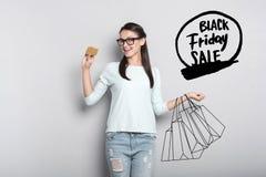 Jolie femme tenant une carte d'or et pensant aux ventes de Black Friday image stock