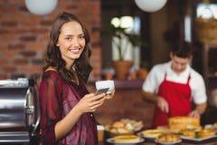 Jolie femme tenant une tasse de café et de textoter Photos libres de droits