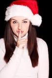 Jolie femme utilisant le chapeau de Santa indiquant le shh Photo stock
