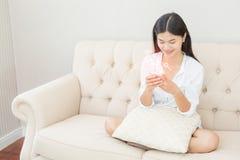 Jolie fille à l'aide de son smartphone sur le divan à la maison dans la vie photo stock