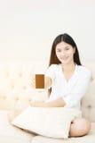 Jolie fille à l'aide de son smartphone sur le divan Image stock