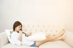 Jolie fille à l'aide de son smartphone sur le divan Photos stock