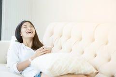 Jolie fille à l'aide de son smartphone sur le divan Photographie stock libre de droits