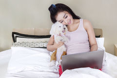 Jolie fille à l'aide du carnet avec son chien sur le lit Images libres de droits