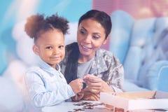 Jolie fille agréable tenant un morceau de puzzle denteux Photos stock