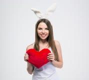 Jolie fille avec des oreilles de lapin tenant le coeur Photos libres de droits