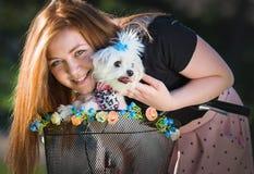 Jolie fille avec la bicyclette et le chien maltais Photographie stock